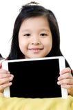 Den lilla asiatiska flickan ler med minnestavladatoren Royaltyfri Foto