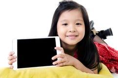 Den lilla asiatiska flickan ler med minnestavladatoren Royaltyfri Fotografi