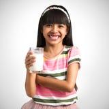 Den lilla asiatiska flickan med ett exponeringsglas av mjölkar Arkivfoton