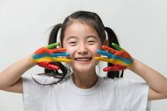 Den lilla asiatiska flickan med händer målade i färgrika målarfärger Royaltyfria Bilder