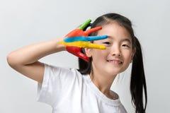 Den lilla asiatiska flickan med händer målade i färgrika målarfärger Fotografering för Bildbyråer