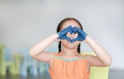 Den lilla asiatiska flickan med hennes blåa händer målade uttryck i hjärtatecken i ungerum arkivfoto
