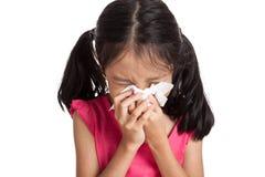 Den lilla asiatiska flickan nyser med servettpapper Arkivfoton