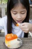 Den lilla asiatiska flickan tycker om den orange ostpajen. Arkivbilder