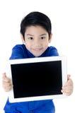 Den lilla asiatiska gulliga pojken ler med minnestavladatoren på isolerade lodisar Fotografering för Bildbyråer