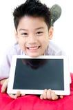 Den lilla asiatiska pojken i studentens likformig med minnestavladatoren är på Fotografering för Bildbyråer