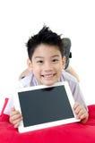 Den lilla asiatiska pojken i studentens likformig med minnestavladatoren är på Royaltyfria Foton