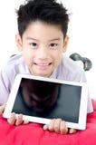 Den lilla asiatiska pojken i studentens likformig med minnestavladatoren är på Royaltyfria Bilder