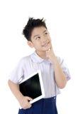 Den lilla asiatiska pojken i studentens likformig med minnestavladatoren är på Royaltyfri Foto