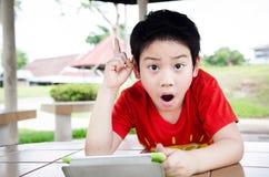 Den lilla asiatiska pojken ler med minnestavladatoren Arkivbild