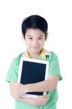 Den lilla asiatiska pojken ler med minnestavladatoren på isolerad backgro Royaltyfri Bild