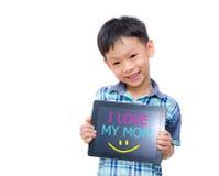 Den lilla asiatiska pojken ler med minnestavladatoren på vit bakgrund Arkivfoto