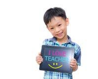 Den lilla asiatiska pojken ler med minnestavladatoren på vit bakgrund Fotografering för Bildbyråer