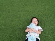 Den lilla asiatiska ungeflickan lägger ner på gräsmattan Royaltyfria Foton