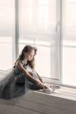 Den lilla ballerina i grå färgklänning sätter på framdelen för pointe för balettskor Royaltyfria Bilder