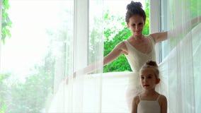 Den lilla ballerina ska upprepa efter läraren Två ballerina är vid det stora fönstret med vita gardiner härligt lager videofilmer