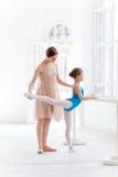 Den lilla ballerina som poserar på balettbarren med Royaltyfri Fotografi