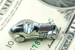Den lilla bilen som göras av krom, lägger på en dollarsedel royaltyfria bilder