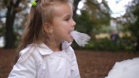Den lilla blonda flickan äter den söta sockervadden i staden parkerar Härlig liten flicka som äter godis-floss Äta för barn arkivfilmer