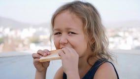 Den lilla blonda flickan äter smörgåsen för frukosten som sitter i terrass lager videofilmer