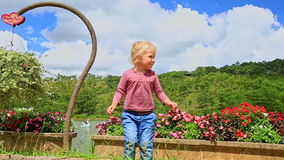 Den lilla blonda flickan ler våghänder vid blomma sjöcloseupen lager videofilmer