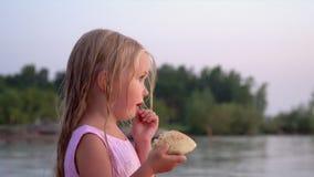 Den lilla blonda flickan på stranden Lilla flickan äter rulle under en nedgång på havet stock video