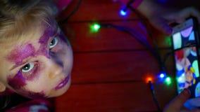Den lilla blonda flickan sitter på golv och spelar på telefonen i lekar Inre i festligt rum Nytt års girlander, på golv arkivfilmer