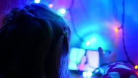 Den lilla blonda flickan sitter på golv och spelar på telefonen i lekar Inre i festligt rum Nytt års girlander, på golv lager videofilmer