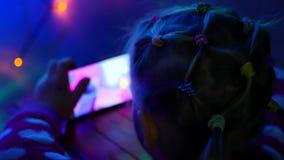 Den lilla blonda flickan sitter på golv och spelar på telefonen i lekar Inre i festligt rum Nytt års girlander, på golv stock video