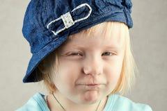 Den lilla blonda flickan skelar ögon Royaltyfri Fotografi