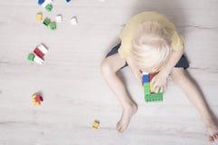 Den lilla blonda pojken är byggande av den kulöra formgivaren Top beskådar fotografering för bildbyråer