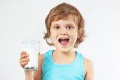 Den lilla blonda pojken med exponeringsglas av nytt mjölkar på vit bakgrund Royaltyfria Bilder