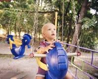 Den lilla blonda pojken på en gunga i en sommar parkerar Royaltyfria Bilder