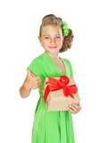 Den lilla brudtärnan med härligt hår i en grön klänning visar ges Royaltyfri Foto
