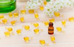 Den lilla bruna flaskan med nödvändiga oljor för nerolien, guld- kapslar av den naturliga skönhetsmedlet och blommor blomstrar på Arkivfoton
