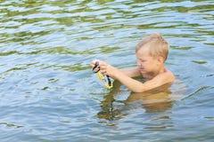 Den lilla Caucasian pojken i simning rullar med ögonen simning i sjön fotografering för bildbyråer