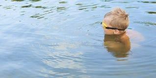 Den lilla Caucasian pojken i simning rullar med ögonen simning i sjön arkivbilder