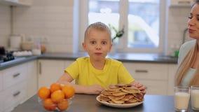 Den lilla caucasian pojken med stora blåa ögon i gul skjorta har gyckel i kök Morgon Sonen med fostrar modernt kök stock video