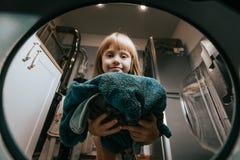Den lilla charmiga flickan sätter kläderna i tvättmaskinen i badrummet royaltyfria foton