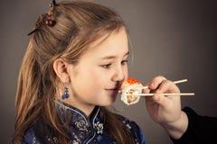 Den lilla charmiga flickan som äter rulle, blidkar ståenden arkivbilder
