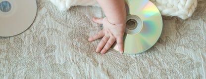 Den lilla discjockeyn, behandla som ett barn lite, CD drev, tar en hand på sängen royaltyfri foto