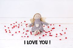 Den lilla dockan med röda hjärtor som sitter på en trävit bakgrund med texten 'älskar jag, dig ', arkivfoto