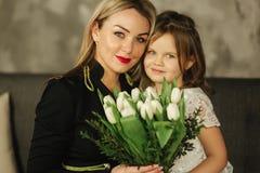 Den lilla dottern ger sig för att fostra buketten av blommor Hemmastadda mamma och dotter Bukett av blommor på 8th marsch royaltyfria bilder