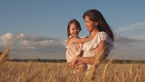 Den lilla dottern kysser mamman på ett vetefält Lycklig familjresor Behandla som ett barn i armarna av mamman modern går med beha arkivfilmer