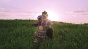 Den lilla dottern lär att gå på solnedgången stock video