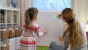 Den lilla dottern och hennes moder drar med färgrika blyertspennor lager videofilmer