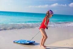 Den lilla förtjusande flickan drar en surfingbräda på den vita kusten Arkivfoto