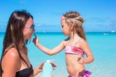 Den lilla förtjusande flickan får solkräm på henne Arkivbild