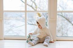 Den lilla förtjusande pojken behandla som ett barn den vita nallebjörnen för kläder som nära sitter Arkivbilder