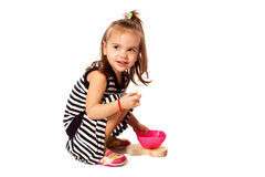 Den lilla flickan äter havreflingor som isoleras på vit Arkivfoton